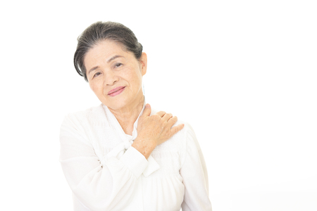 Old woman who has a shoulder pain. Stock Photo