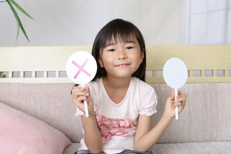 Asian girl with a Yes or No sign Stock Photo