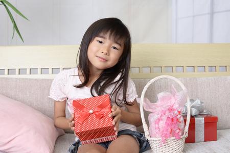 彼女の手でプレゼントを持ってうれしそうな女の子