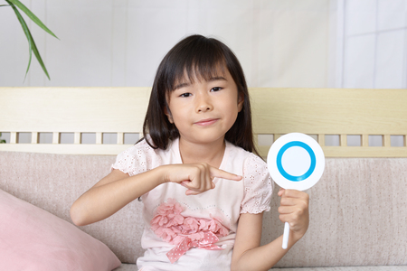 Smiling Asian girl with a Yes sign Stock Photo