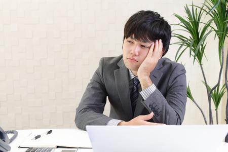 Moe en gestrest Aziatische zakenman