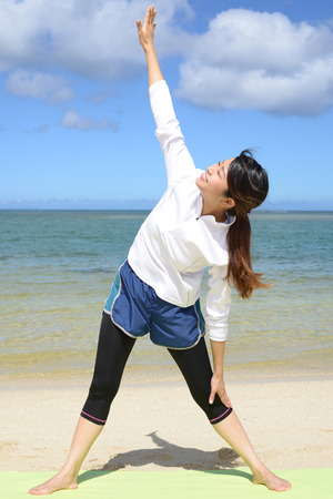 Woman have a stretch on the beach. Stock Photo