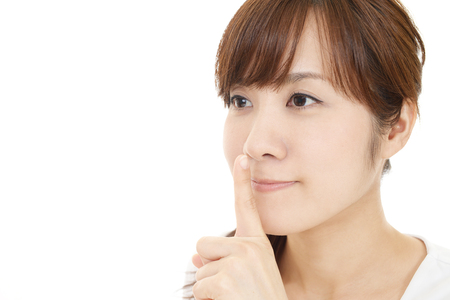 Portrait of a woman making silence gesture Stock Photo