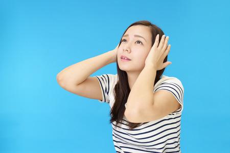 Woman who holds her ears Foto de archivo