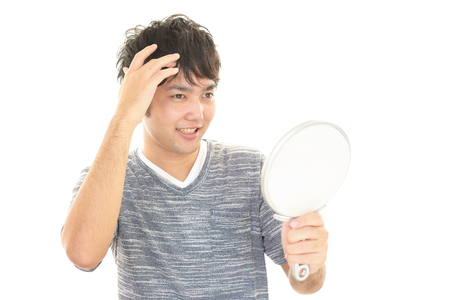 Asian man looking at his hair in mirror Stock Photo