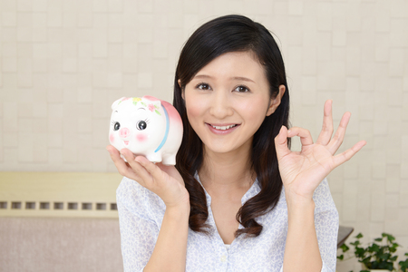 Smiling young woman with a piggy bank