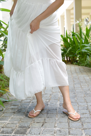 A woman in white dress wearing flip flops