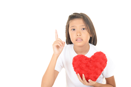 A girl holding a red heart showing her index finger