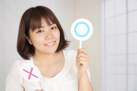 Woman with a Yes or No sign 写真素材