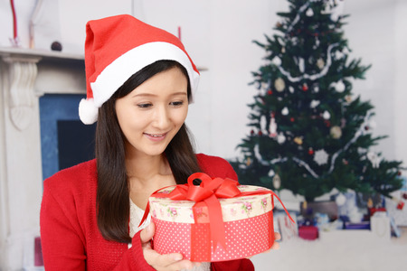 Young woman in Santa Claus cap with a present Stock Photo