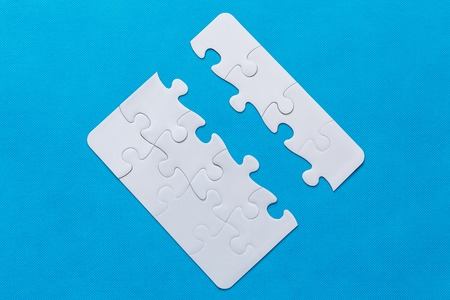 Jigsaw Puzzle with missing piece. Blue background.