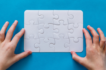 abstract puzzle background with piece missing. blue background. people hand