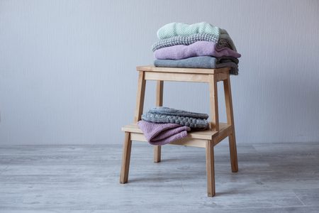 Stack of cozy knitted clothes on a wooden ladder. G Stock fotó