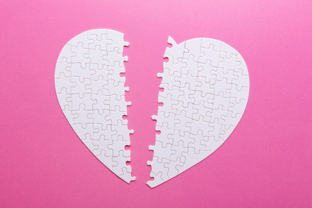 White puzzle broken heart on pink background. Missing piece. Top view