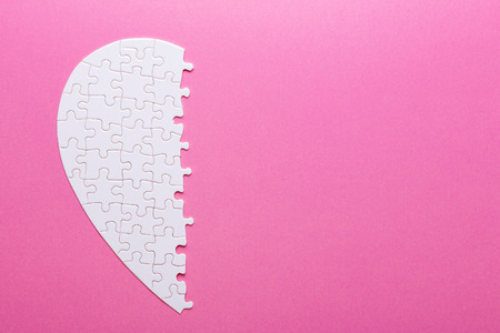White puzzle part of heart on pink background. Missing piece. Top view Stock Photo