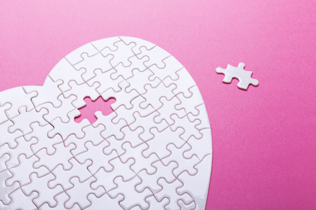 White puzzle heart on pink background. Top view