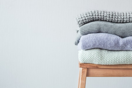 Stack of cozy knitted clothes on a wooden ladder. Gray wall. Vintage tinting