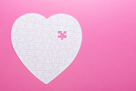 White puzzle heart on pink background. Missing piece. Top view