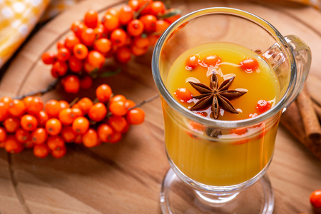 Hot beverage of sea-buckthorn berries in glass cup on wooden background. Rustic style.