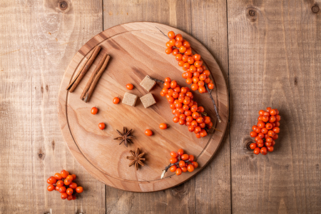 Sea-buckthorn berries and spice on wooden background. Rustic style. Top view