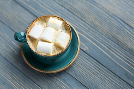 Cup of coffee, marshmallow on wooden background. Warm lights. Cozy winter morning. Lifestyle concept. Selective focus.