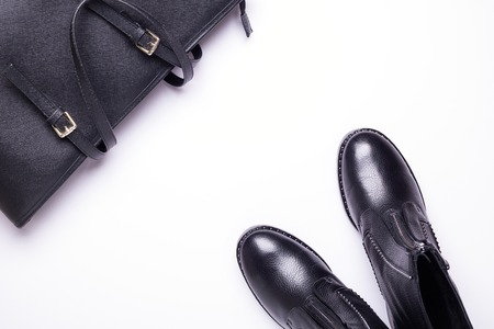 Woman accessory. Black stylish boots, black luxury leather bag on white background. Top view background. Flat lay. Copy space.