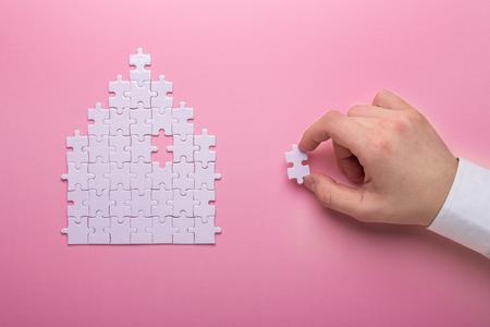 Casse-tête blanc. Puzzle en forme de maison. Le concept de loyer, hypothèque. Main tenant un morceau de puzzle blanc. Fond rose. Vue de dessus Vue de dessus. Espace de copie Banque d'images