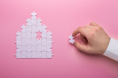 White puzzle. House shape puzzle. The concept of rent, mortgage. Hand holding piece of white puzzle. Pink background. Top view Top view. Copy space