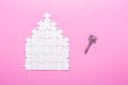 White puzzle. House shape puzzle and key. The concept of rent, mortgage. Pink background. Top view. Copy space