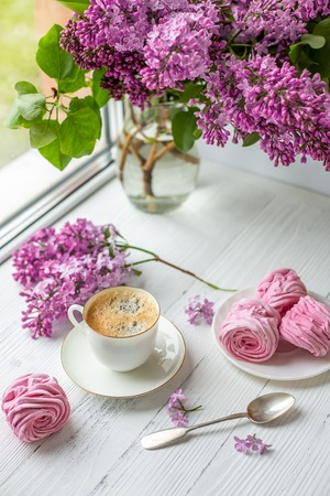 Bouquet of lilacs, cup of coffee, homemade marshmallow. Romantic spring morning. Stockfoto