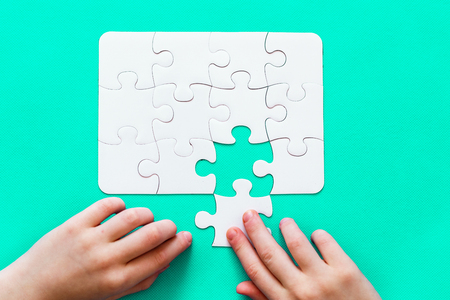 Jigsaw Puzzle with missing piece on mint background Top view People hand