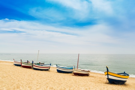 Beautiful multicolored wooden fishing boats on a sandy beach in sunny day. Place for text Imagens