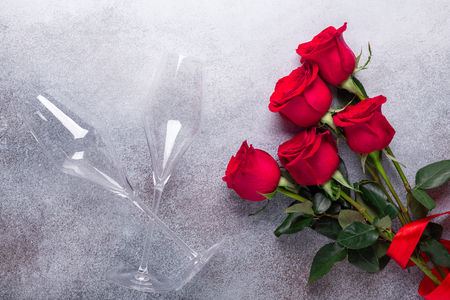 Red rose flowers bouquet, champagne glasses on stone background Valentine's day greeting card Copy space Top view