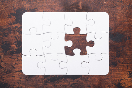Jigsaw Puzzle with missing piece on old wooden background Top view Standard-Bild - 116380721