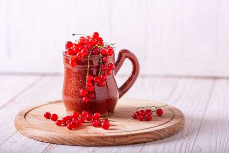 Fresh red currant in a ceramic cup on a white wooden background Healthy food 版權商用圖片