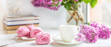 Bouquet of lilacs, cup of coffee, homemade marshmallow and stack of books on window sill Romantic spring morning. Selective focus