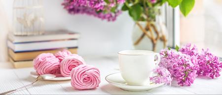 Bouquet von Flieder, Tasse Kaffee, hausgemachtem Marshmallow und Stapel Bücher auf der Fensterbank Selektiver Fokus Standard-Bild