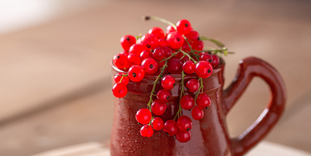Ceramic cup with fresh red currant on a wooden background Rustic style Healthy food