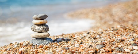 Balance of stones on the beach, sunny day. Sand on the beach Banner