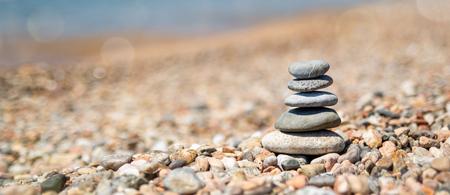 Balance of stones on the beach, sunny day. Sand on the beach Banner