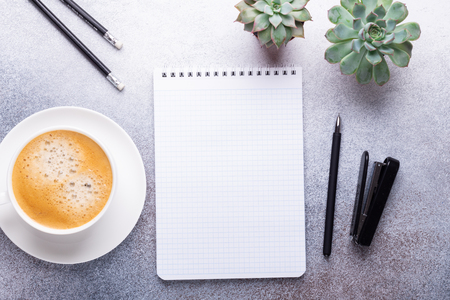 Office workplace with cup of coffee, succulent, note pad and pen. Top view. Stone background. Copy space 写真素材