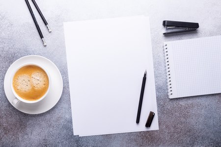 Office workplace with blank paper, cup of coffee, note pad and pen. Top view. Stone background. Copy space