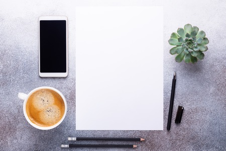 Office workplace with blank paper, cup of coffee, smartphone and pen. Top view. Stone background. Copy space
