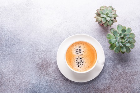Cup of coffee and succulent on stone background. Office workplace. Top view. Copy space