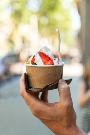 Hand holding paper cup with ice cream on blurred backgruond Street food Selective Focus
