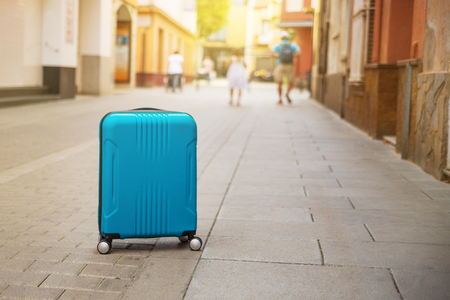 Blue suitcase on European city street, tourism in Europe, travel background Copy space 写真素材