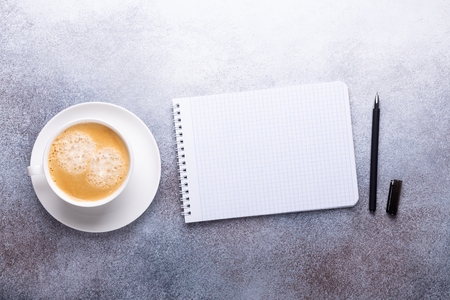 Office workplace with cup of coffee, note pad and pen. Top view. Stone background. Copy space
