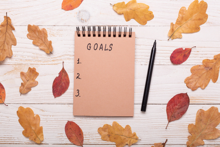 Autumn leaves, notebook and pencils on a white wooden background. Flat lay, top view, copy space.