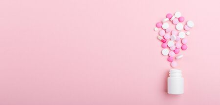 Pink and white pills on pink background Plastic bottle Heap of assorted various medicine tablets and pills Health care Copy space Top view Horizontal banner 写真素材