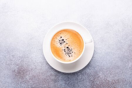 Cup of coffee on stone background. Office workplace. Top view. Copy space 写真素材